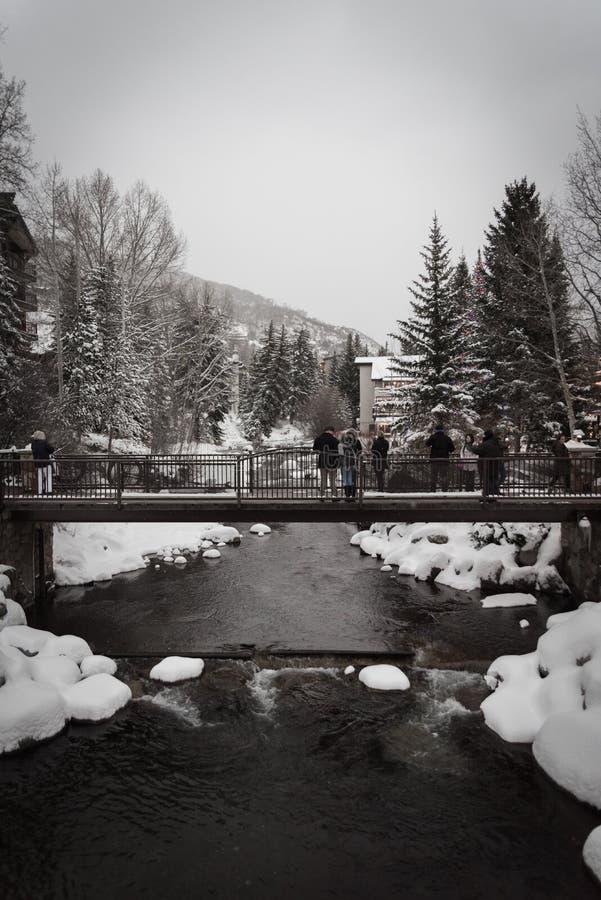 Ein Fluss, der unter eine Schneeüberdachte brücke in Vail, Colorado läuft lizenzfreies stockfoto