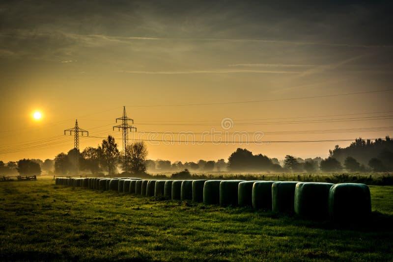 Ein foogy Morgen mit Heuballen während des Sonnenaufgangs lizenzfreie stockbilder