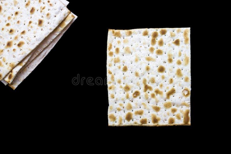Ein Foto von zwei Stücken Matzah oder matza lokalisiert auf schwarzem Hintergrund Matzah für die jüdischen Passahfestfeiertage Pl lizenzfreie stockbilder