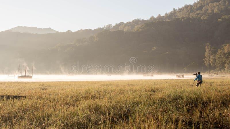 Ein Fotograf, der Landschaft Balis Indonesien während des Sonnenaufgangs schießt lizenzfreie stockbilder