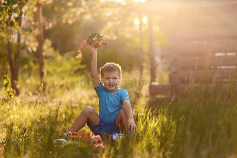 Ein fröhlicher 5-jähriger Junge in einem blauen T-Shirt und Shorts spielt im Sommer mit Plastikautos auf dem Gras im Park lizenzfreie stockfotos