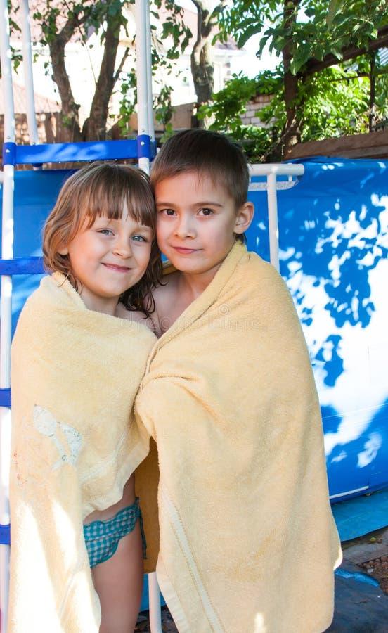 Ein fröhliches Mädchen und ein Junge werden in einem Tuch eingewickelt stockbilder