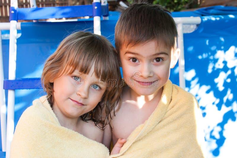 Ein fröhliches Mädchen und ein Junge werden in einem Tuch eingewickelt stockfotografie
