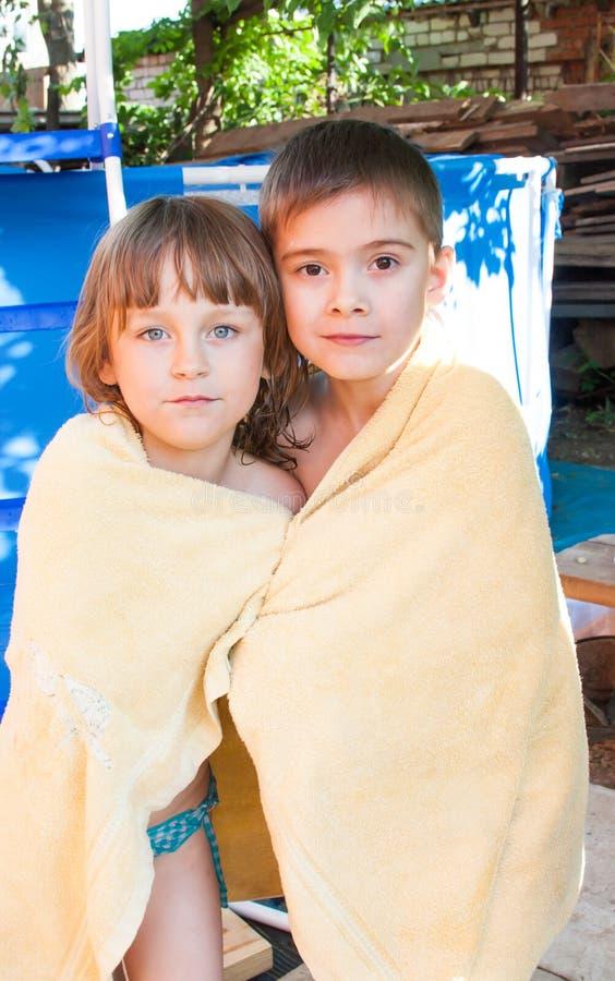 Ein fröhliches Mädchen und ein Junge werden in einem Tuch eingewickelt lizenzfreies stockfoto