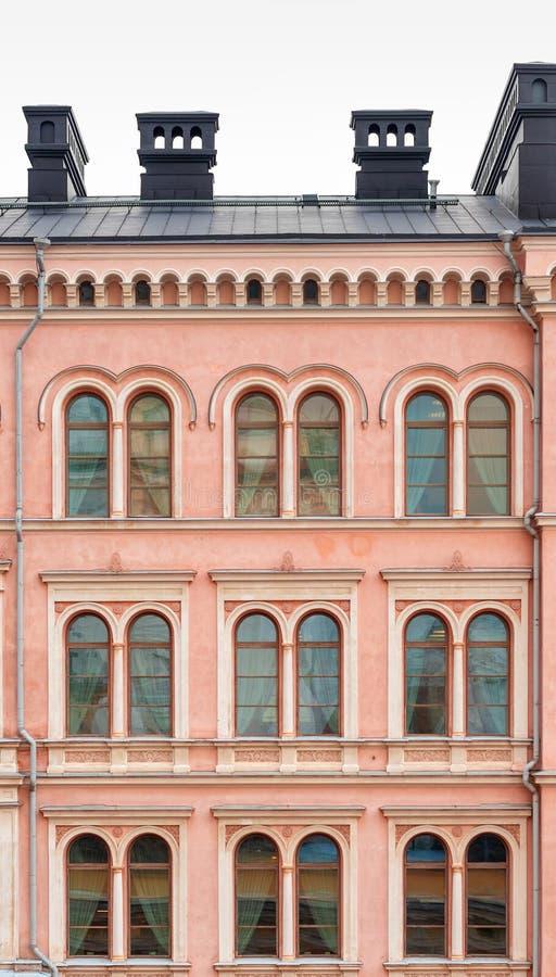 Ein Fragment der Fassade eines schönen rosa Stadtgebäudes Windows mit einem halbkreisförmigen Teil lizenzfreie stockfotos