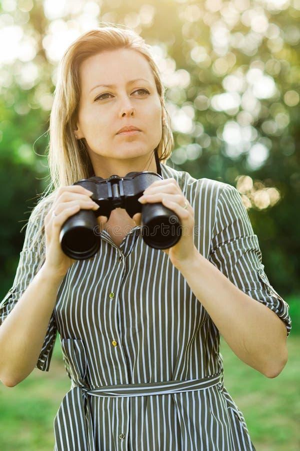 Ein Frauenforscher wird die schwarzen Ferngläser benutzen - im Freien stockfotografie