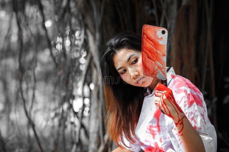 Ein Frauenholdingmesser mit Blut im Park, Halloween-Konzept lizenzfreies stockfoto