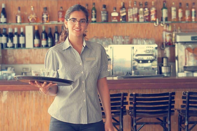 Ein Frauenkellner trägt eine Bestellung lizenzfreie stockbilder
