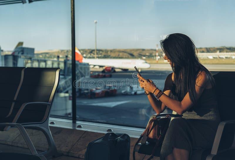 Ein Frauenreisender, der Handy beim Sitzen im Flughafen wartet ihren Flug verwendet lizenzfreie stockfotografie