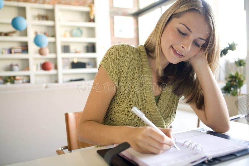 Ein Frauenschreiben in ihrer Tagesordnung lizenzfreie stockfotos