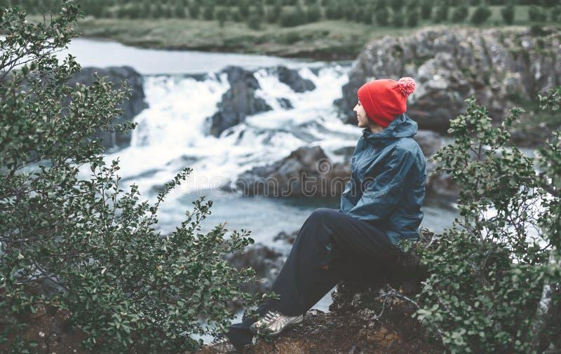 Ein Frauentourist sitzt auf der Bank des Gebirgsflusses mit kleinem Wasserfall lizenzfreie stockbilder