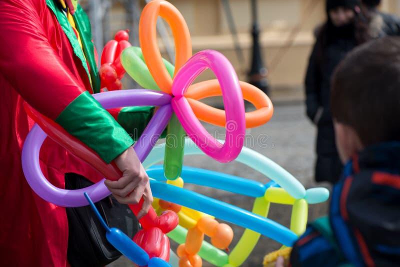 Ein freiberuflich tätiger Clown, der Ballontiere und verschiedene Formen Festival am im Freien im Stadtzentrum schafft stockfoto