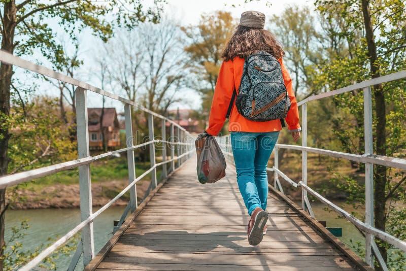 Ein Freiwilliger der jungen Frau mit gesammelt entlang dem Flussabfall in einer Tasche, gehend auf die Brücke Das Konzept des Tag lizenzfreies stockbild