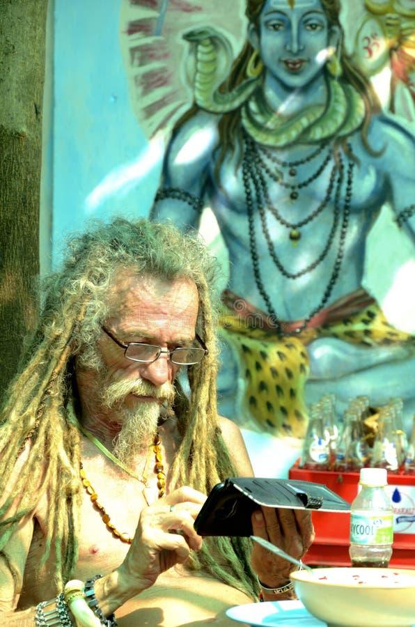 Ein fremder Tourist, der Handy mit Hintergrund des Bildes des hindischen Gottes Shiva verwendet stockbild