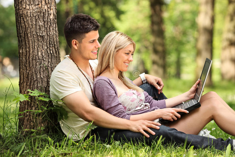 Ein Freund und eine Freundin, die an einem Laptop arbeiten lizenzfreie stockbilder