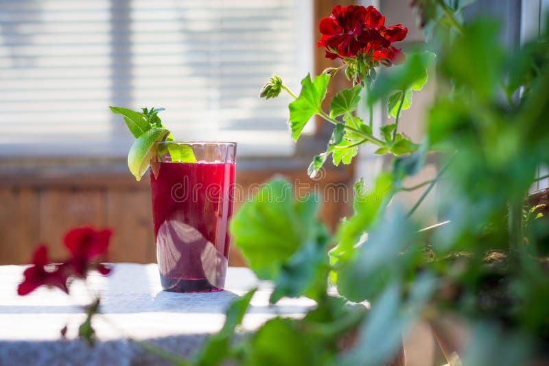 Ein frisches saftiges Glas Frucht- und Beerengetränkstände auf einem Rundtisch mit einer hellen Leinentischdecke stockfoto