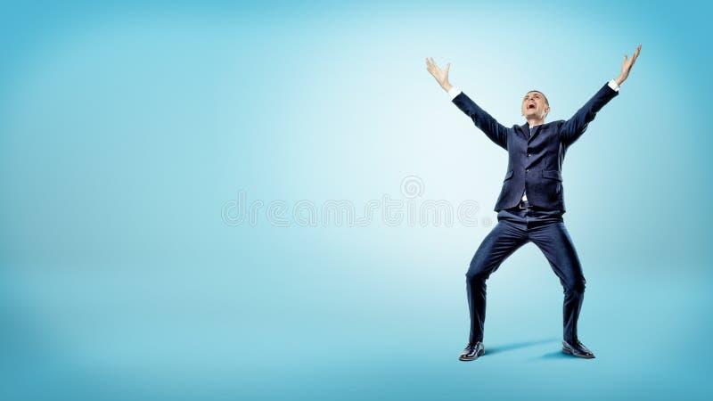 Ein froher Geschäftsmann mit einem Lächeln auf seinem Gesicht und Händen hob in Siegbewegung an stockfotografie