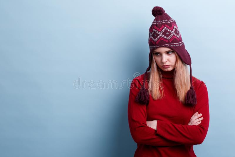 Ein frustriertes Mädchen in einem warmen Hut und in den Bonbons, gekreuzte Arme über Kasten und mit einem beleidigten Blick unten lizenzfreies stockfoto