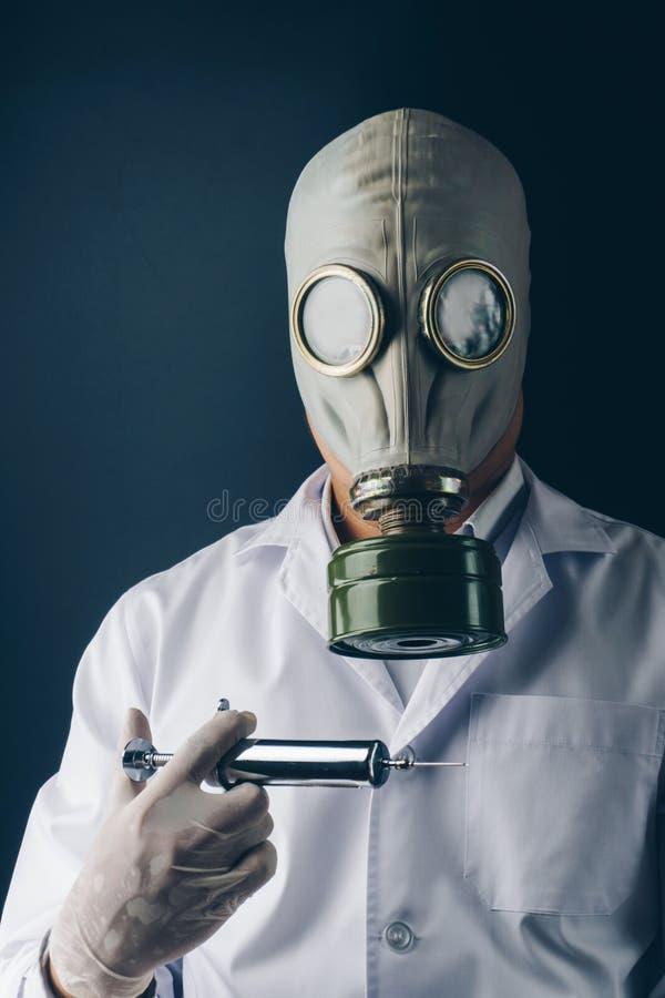 Ein furchtsamer Doktor in der Gasmaske mit einer großen Edelstahlspritze stockbilder
