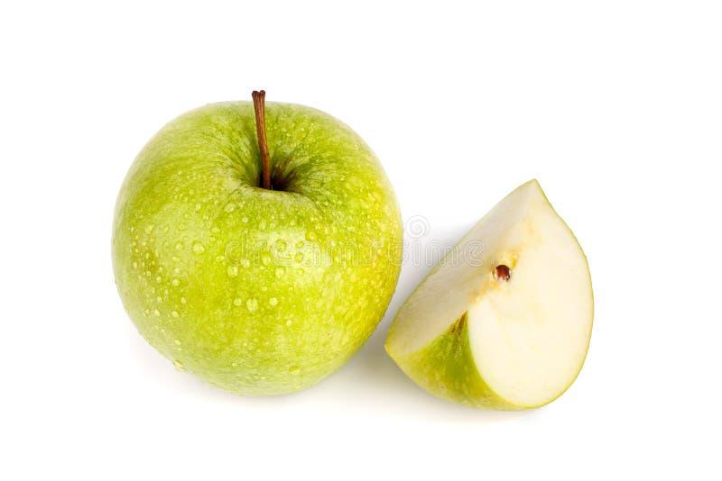 Ein ganzer großer grüner Apfel und Viertel des Apfels in den Wassertropfen auf weißer Hintergrund lokalisiertem Abschluss herauf  stockfotos