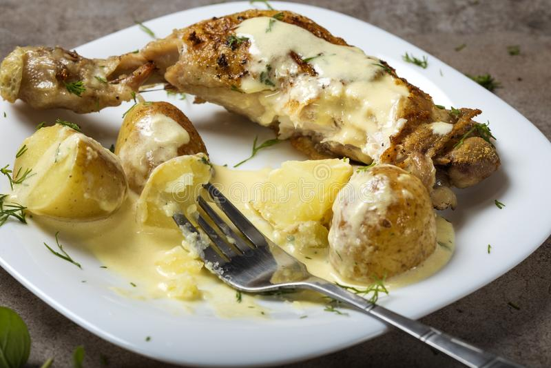 Ein gebratenes Hühnerbein mit Frühkartoffeln und Sauerrahm sauce lizenzfreies stockbild