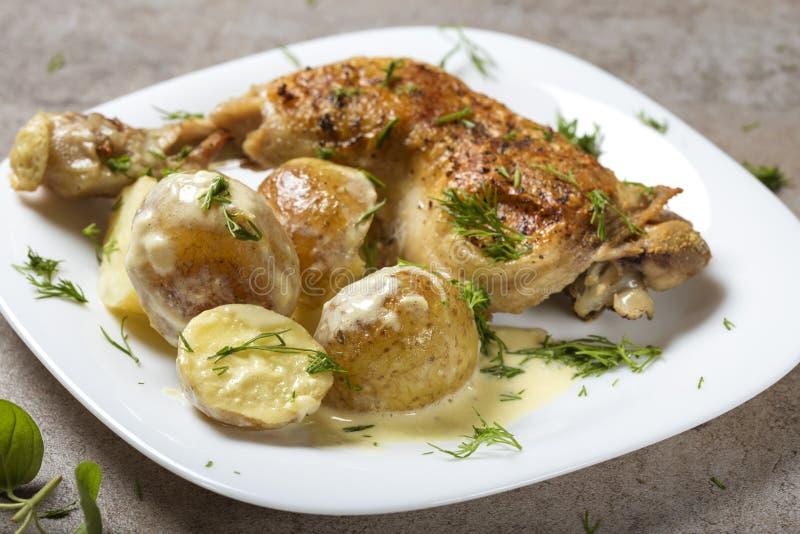 Ein gebratenes Hühnerbein mit Frühkartoffeln und Sauerrahm sauce lizenzfreies stockfoto
