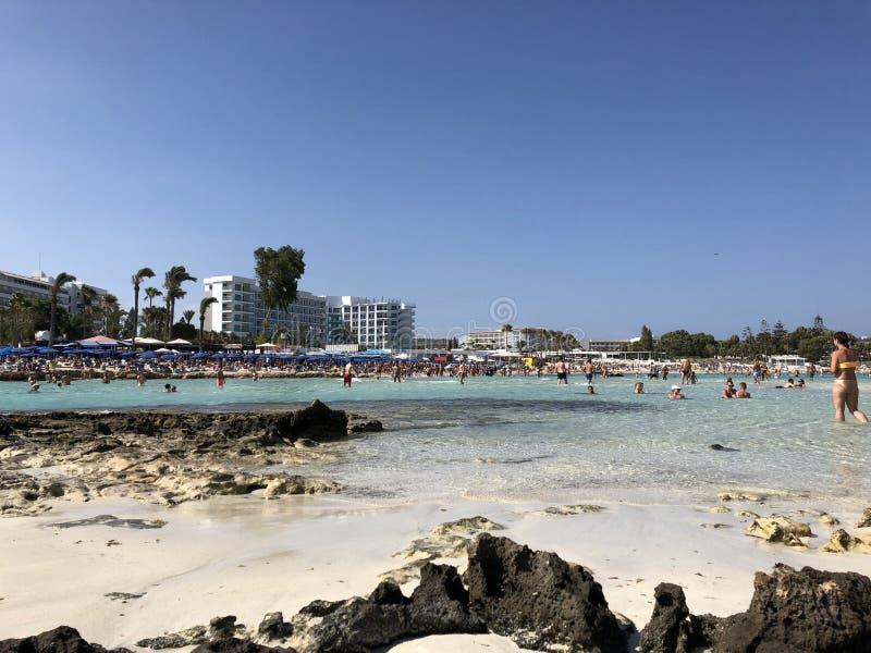 Ein gedrängter Seestrand mit klarem Türkiswasser und weißem Sand an einem heißen Sommertag zypern stockfotografie