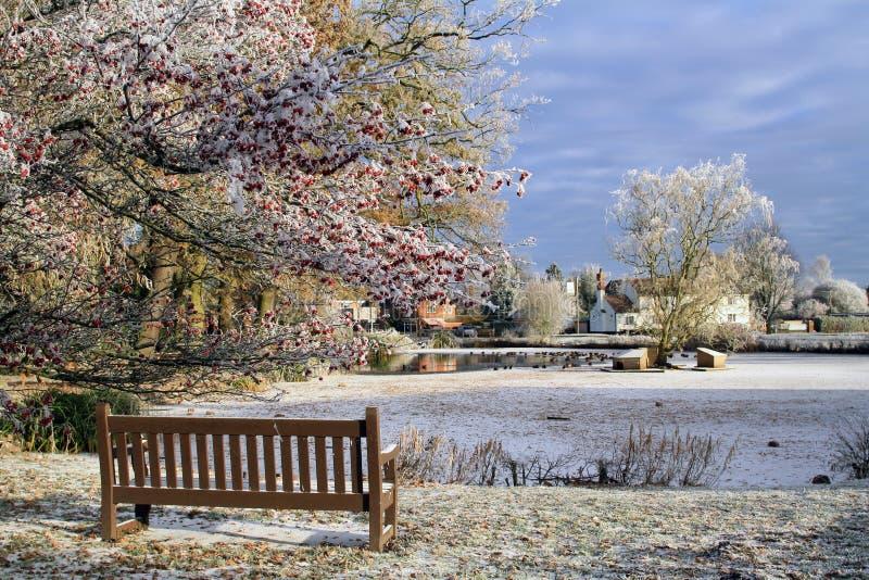 Ein gefrorener Ententeich in einem englischen Dorf mit einer Bank im Vordergrund An einem kalten eisigen Wintertag Hanley Swan, W lizenzfreie stockfotos