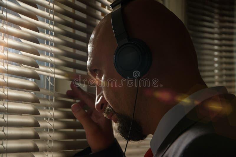 Ein geheimer FBI-Agent peitscht durch die Jalousien und hört eine Unterhaltung in Kopfhörern stockbild