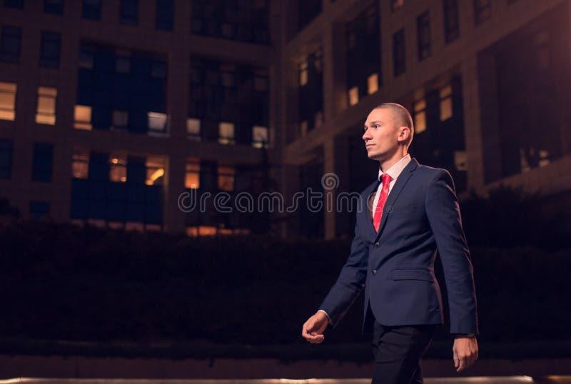 Ein gehender Geschäftsmannanzug des jungen erwachsenen Mannes, formelle Kleidung, übertreffen stockbild