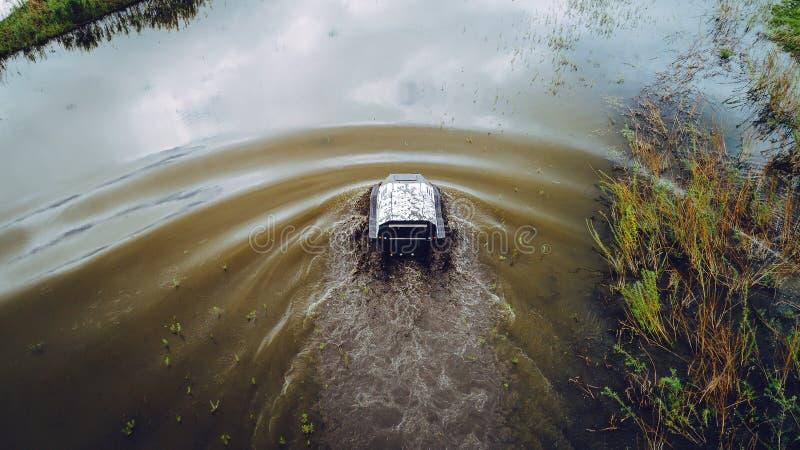 Ein Geländefahrzeug segelt auf den Fluss Antenne über Ansichtspitze stockbild