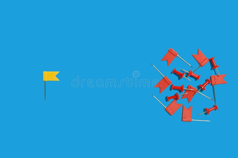Ein gelbe Stiftflaggen, die gegen viele roten Druckbolzen liegen stockfoto