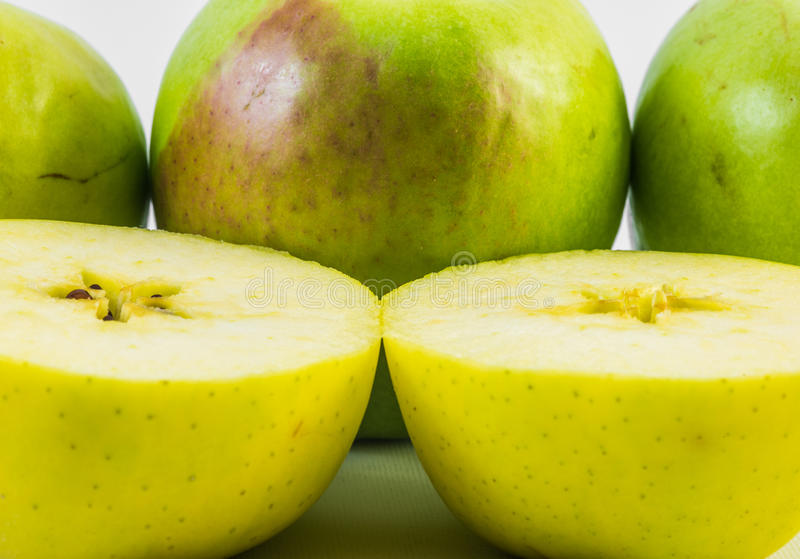 Ein gelber Apfel schnitt zur Hälfte auf einem weißen Hintergrund mit Äpfeln lizenzfreie stockfotos