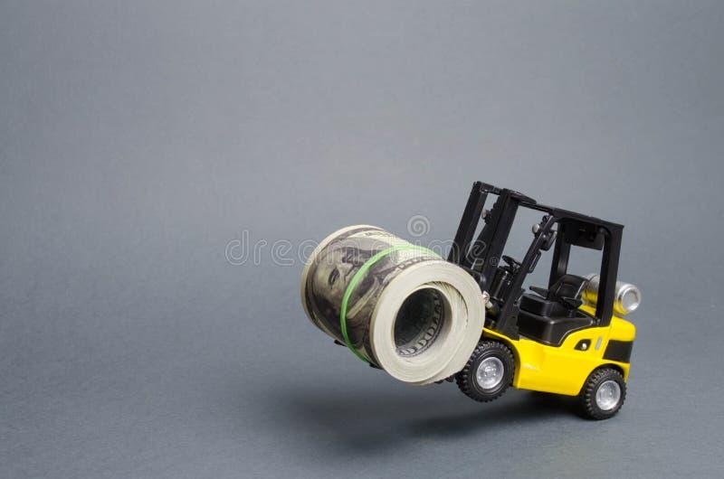 Ein gelber Lader steht auf den Hinterrädern, die ein großes Bündel Dollar halten Konzept der Anziehung der Investition, Ausgabe k lizenzfreie stockfotos