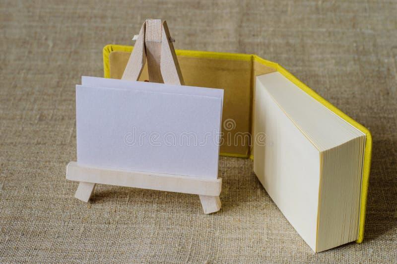 Ein gelbes Mininotizbuch und ein kleines hölzernes Gestell lizenzfreies stockbild