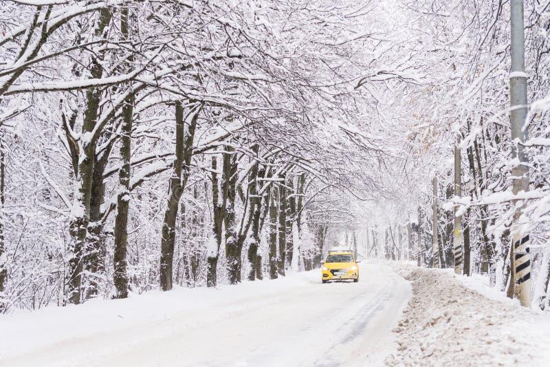 Ein gelbes Taxi reitet entlang die Winterstraße Viel Schnee Das DA lizenzfreie stockbilder
