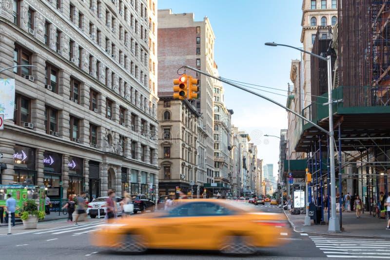 Ein Gelbtaxi beschleunigt hinter Mengen von den Leuten, die einen beschäftigten Schnitt auf 5. Allee in Manhattan New York City k lizenzfreies stockfoto