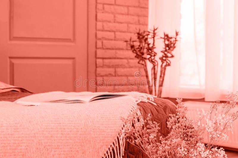 Ein gemütlicher Raum mit einem Bett und ein großes Fenster in der korallenroten Farbe stockbilder