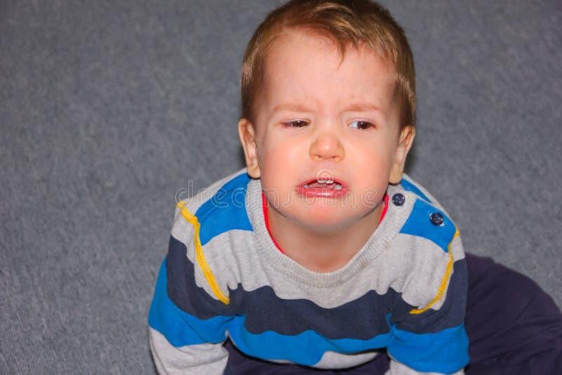 Ein geraspeltes und verletztes Kind sitzt auf dem Boden Der kleine Junge geschmollt stockfotos