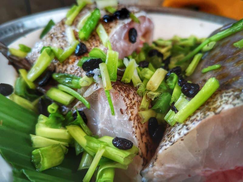 Ein gesäuberter Barschfisch wird mit schwarzen Bohnen vorbereitet und einige Hauptbestandteile ist bereit zu dämpfen stockfotografie
