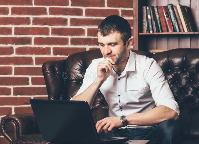 Ein Geschäftsmann arbeitet an Laptop im Büro Er sitzt am Tisch auf dem Hintergrund einer dekorativen Wand in Form von Ziegelstein stockfotos