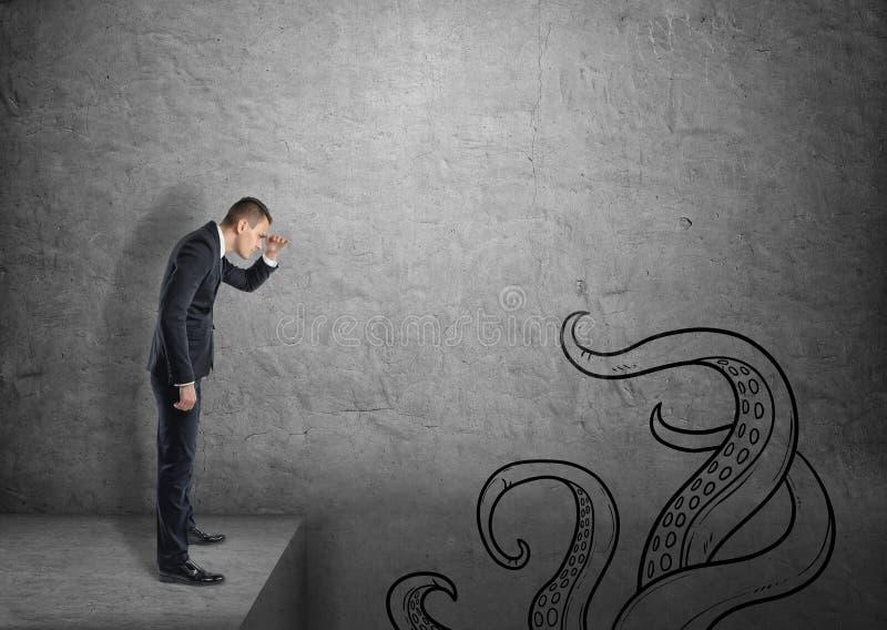 Ein Geschäftsmann auf grauem konkretem Hintergrund untersucht unten einen Abgrund, der mit gezogenen Tentakeln kriecht lizenzfreie stockbilder