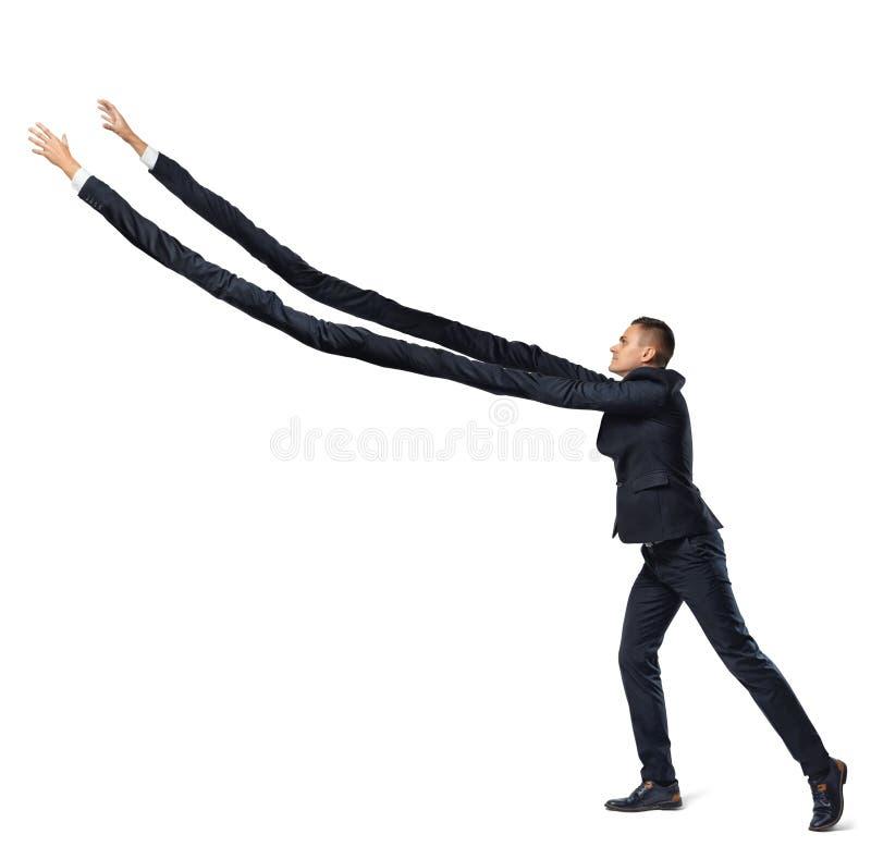 Ein Geschäftsmann auf weißem Hintergrund in der Seitenansicht mit den extrem langen Armen, die versuchen, etwas oben zu ergreifen stockfoto