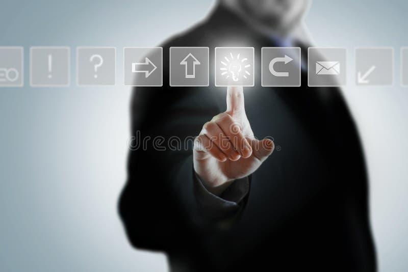 Ein Geschäftsmann, der auf Geschäftsikonen in einem Hologramm klickt stockfoto