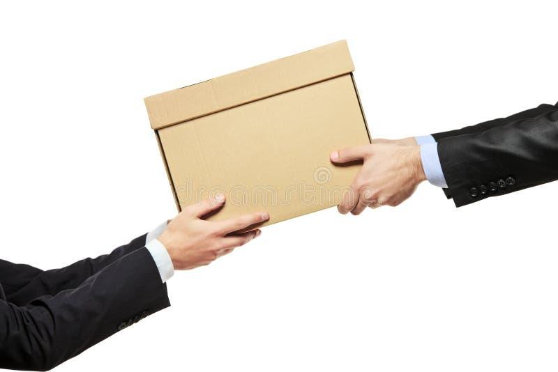 Ein Geschäftsmann, der ein Paket an einen Mann liefert lizenzfreie stockbilder