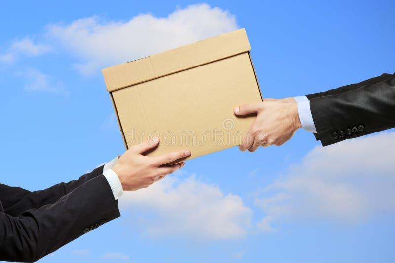 Ein Geschäftsmann, der ein Paket an einen Mann liefert lizenzfreie stockfotos