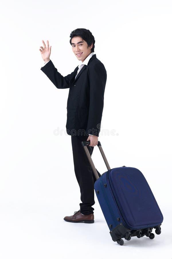 Ein Geschäftsmann, der Gepäck zieht und Hand wellenartig bewegt lizenzfreies stockbild