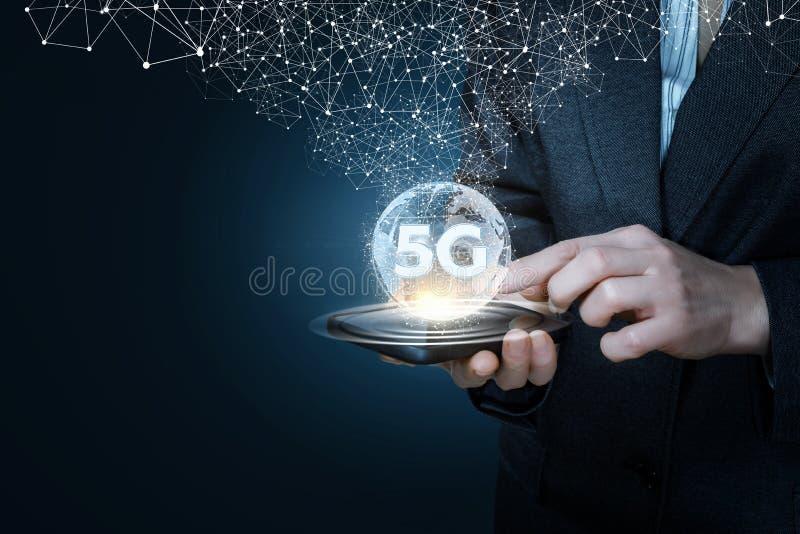 Ein Geschäftsmann, der ein Gerät mit einer globalen Karte und Symbol 5G auf ihm hält lizenzfreie stockfotos