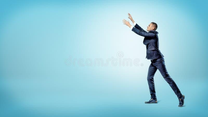 Ein Geschäftsmann in der Seitenansicht mit beiden Händen hob oben versuchen an, etwas oben zu fangen stockbild