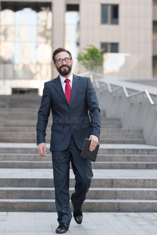 Ein Geschäftsmann, der unten in die Büromitte mit einer Tablette in der Hand geht Erfolgreicher bärtiger Geschäftsmann ist glückl lizenzfreie stockfotos